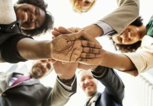 5 people with hands together as a 5 steps to building your website