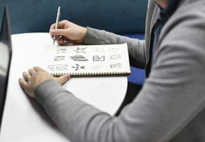Graphic Designer With his Sketchbook working on Logo Design at Webcraff Studio UK